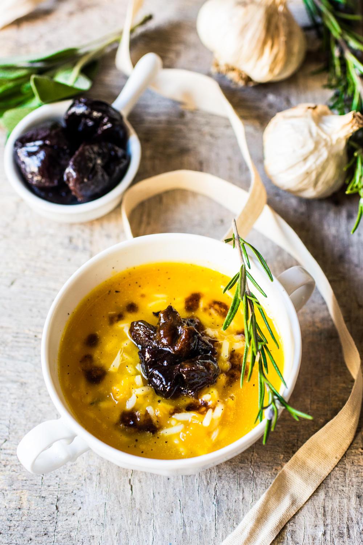 Zuppa di zucca e riso con aglio arrostito e prugne stufate